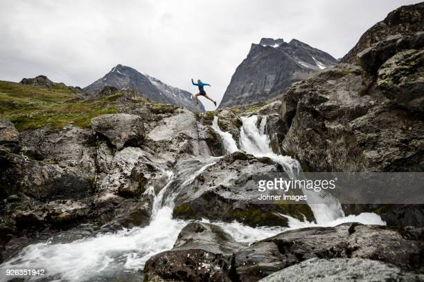 Person jumping over mountain river