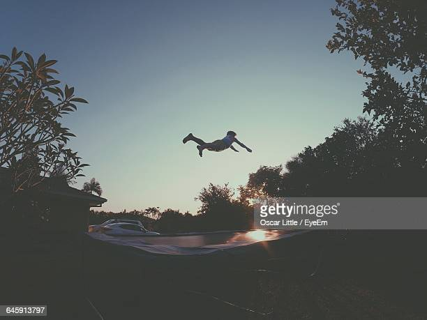 Person Jumping Over Trampoline In Back Yard Against Sky During Sunset
