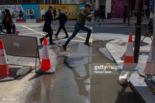 A person jumps over a puddle left in a road on Oxford Street after heavy rain the previous day on 1st May in London England