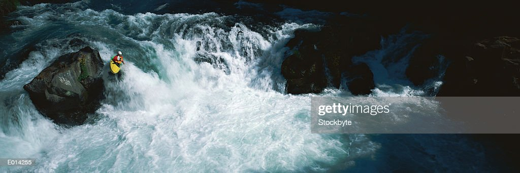 Person kayaking through rough river : Stock Photo