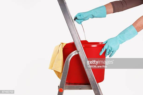 person keeping plastic bucket on step ladder - daily bucket stock pictures, royalty-free photos & images