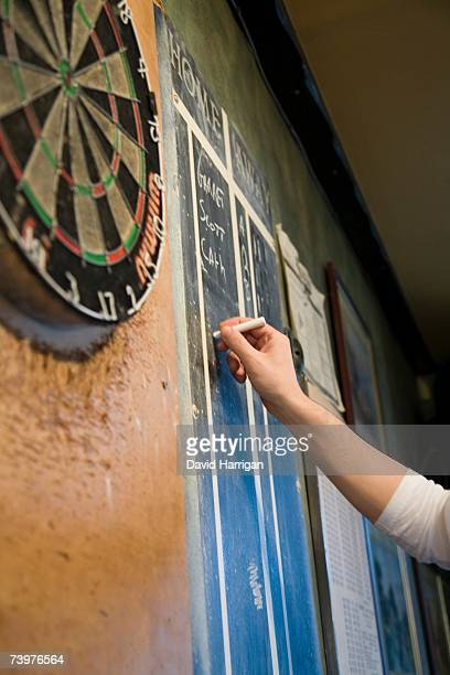 Person keeping score on a blackboard during a game of darts