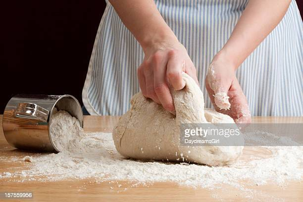 A person kneading dough in the bread making process