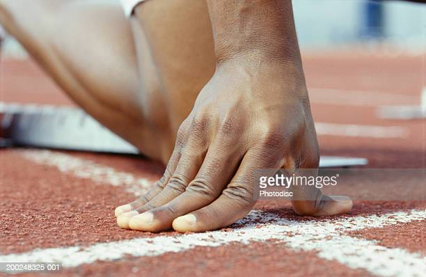 person kneeling with hands on starting line, close-up of hand - commencement photos et images de collection