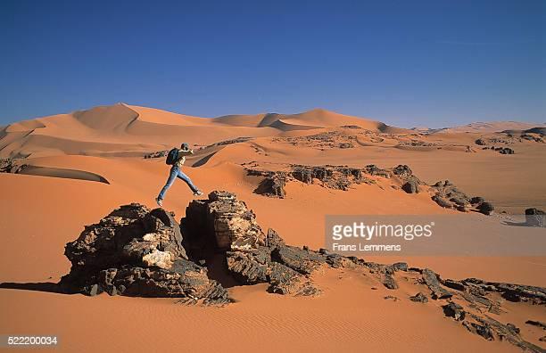 person leaping across rocks in desert