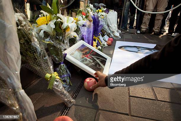 A person leaves an apple at a makeshift shrine to commemorate Steve Jobs cofounder and former chief executive officer of Apple Inc outside the...