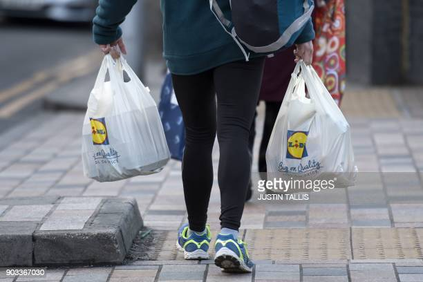 Person leaves with their goods in plastic carrier bags after shopping at a branch of Lidl in south Londo on January 10, 2018.
