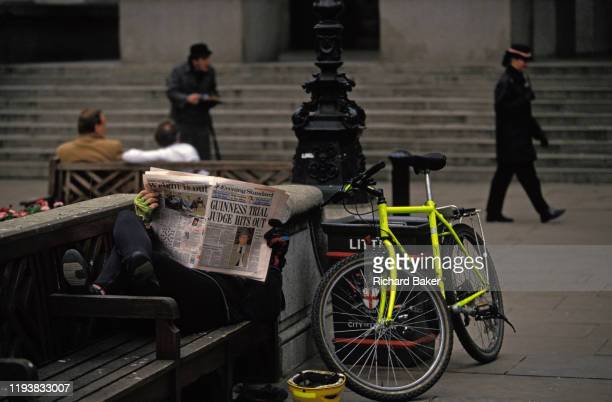 Person lies on a bench reading an Evening Standard newspaper carrying a headline about the Guinness trial, on 27th May 1991, in the City of London,...