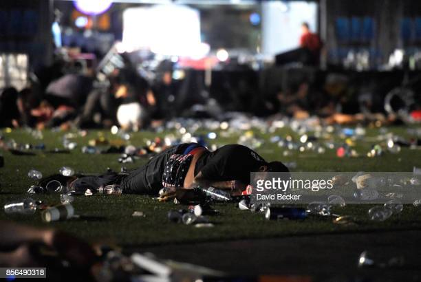 A person lies on the ground at the Route 91 Harvest country music festival after apparent gun fire was heard on October 1 2017 in Las Vegas Nevada...