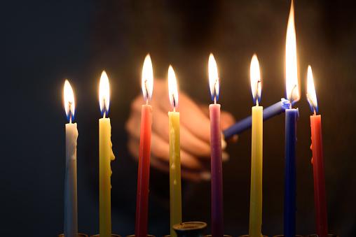 A person lighting Hanukkah Candles in a menorah. 1178875786