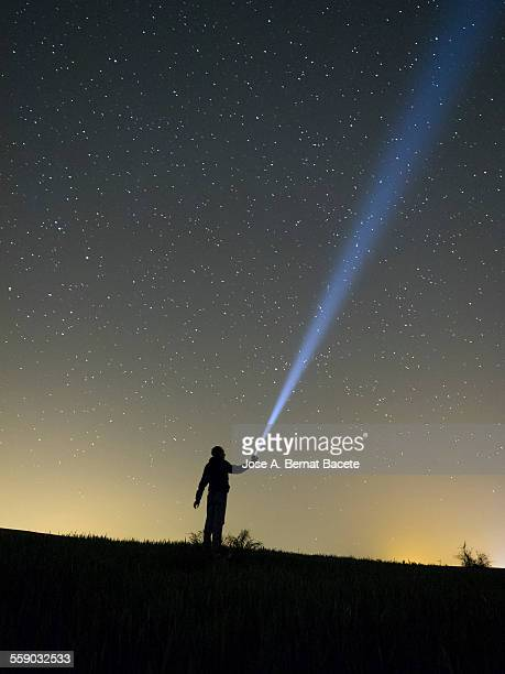 Person lighting the sky with a flashlight