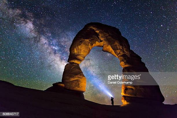 person lightning up the milky way at delicate arch - delicate arch stock pictures, royalty-free photos & images