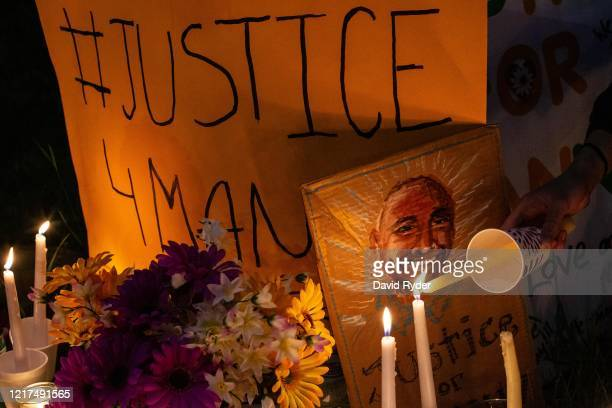 A person lights a candle at a vigil for Manuel Ellis a black man whose March death while in Tacoma Police custody was recently found to be a homicide...
