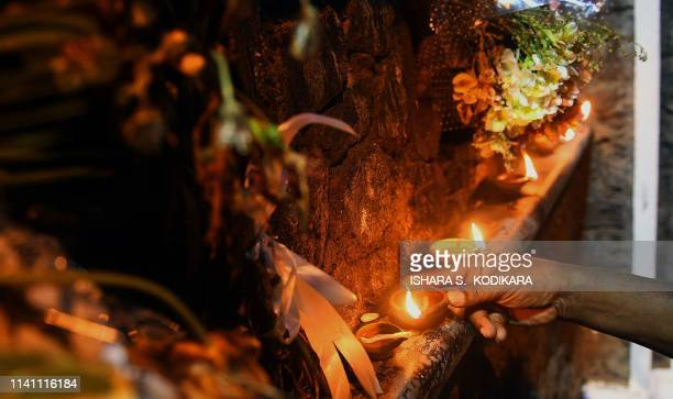 A person lights coconut oil lamps for the victims of Easter sunday bomb blasts at St Sebastian's Church in Negombo near Colombo on May 4 2019 Sri...