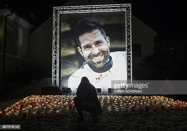 TOPSHOT A person lights up a candle in front of a picture of Austrian racing pilot Hannes Arch during a memorial service in Trofaiach Austria on...