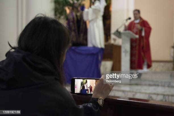 A person live broadcasts a Palm Sunday mass at in Caracas Venezuela on Sunday April 5 2020 Amid the coronavirus as the world's major religions enter...