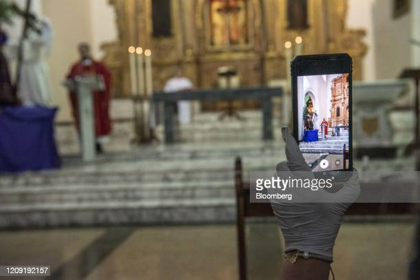 A person live broadcasts a Palm Sunday mass in Caracas Venezuela on Sunday April 5 2020 Amid the coronavirus as the world's major religions enter one...