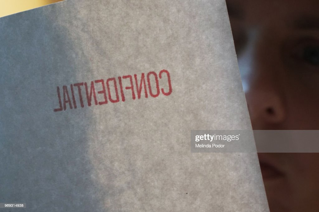 Person looking at a document marked confidential : Stock Photo