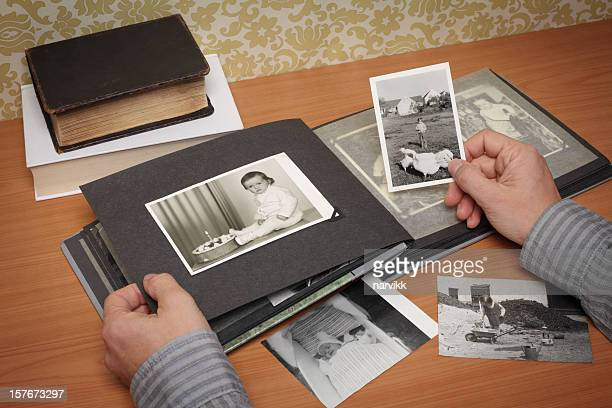 person looking at the album with old photographs - childhood photo album stock photos and pictures