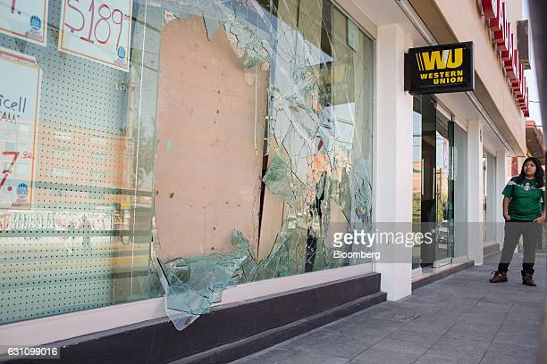 A person looks at a broken window of a pharmacy that was looted during protests against the gasoline price hike in Mexico City Mexico on Friday Jan 6...