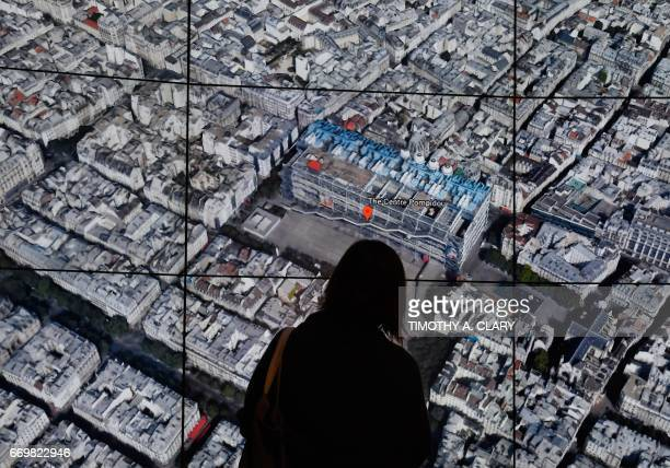 A person looks at a Google Earth map of Paris France on a screen as Google Earth unveils the revamped version of the application April 18 2017 at a...
