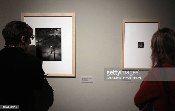 A person looks at a picture by HungarianBorn US photographer Andre Kertesz square Jolivet Paris la nuit dated 1927 on September 27 2010 at the Jeu de...