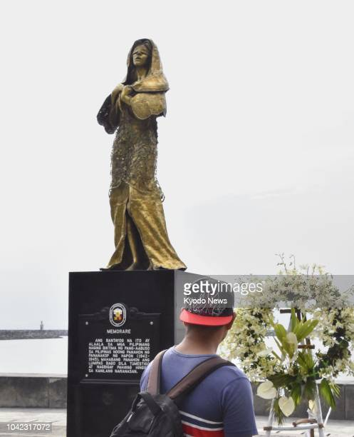 """Person looks at a statue symbolizing Filipino """"comfort women,"""" who were forced to work in Japanese brothels during World War II, in Manila in..."""