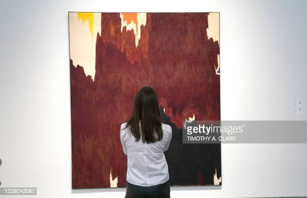 """Person looks at Clyfford Still's """"1957-G"""" during a press preview at Sotheby's October 23, 2020 for the upcoming Sothebys Impressionist & Modern Art..."""