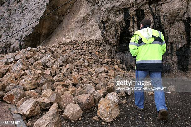 A person looks at fallen rocks blocking a road in RoquebrunecapMartin southeastern France on January 18 2014 Many roads have been cut in the...