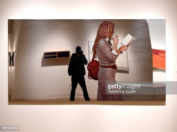 A person looks at Michelangelo Pistoletto Turista Che Mangia Un Panino on display during the media preview on November 4 2016 for Sothebys New York...