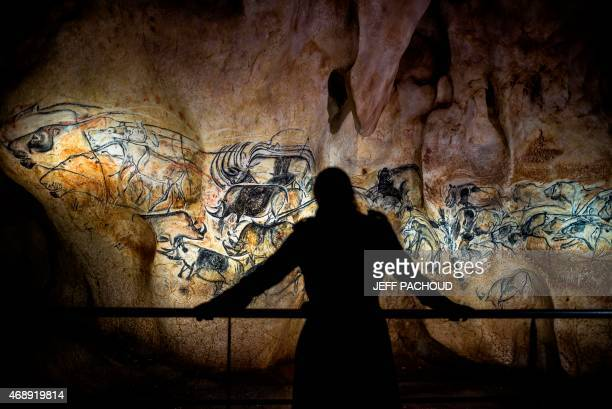 Person looks at part of the full-scale reproduction of frescos found at the cave of Pont-D'Arc also known as the Chauvet cave, on April 8, 2015 in...