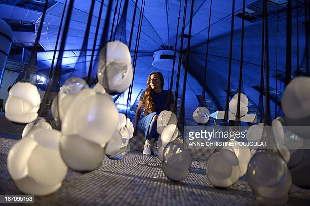 A person looks at the art creation 'PIP Show' by French artist Camille Lorin made with fishnet stockings containing breast implants from the Poly...
