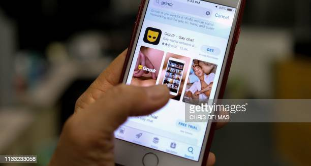 A person looks at the Grindr app in the App Store on a phone in Los Angeles on March 27 2019 A Chinese firm has been ordered by American national...