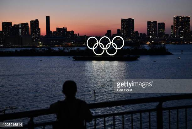 Person looks at the Tokyo 2020 Olympic Rings on March 25, 2020 in Tokyo, Japan. Following yesterdays announcement that the Tokyo 2020 Olympics will...