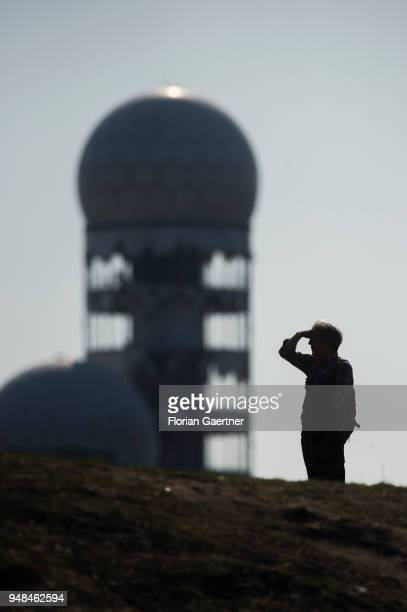 A person looks into the distance on April 08 2018 in Berlin Germany In the background there is a building of the former air traffic control and...