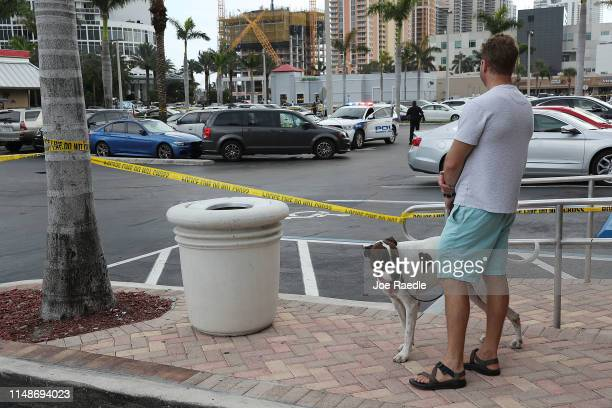 A person looks on as a Sunny Isles Beach police officer stands near a van where an individual was found shot to death after a shooting close by that...