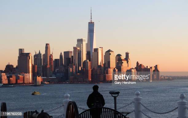 A person looks out at the skyline of lower Manhattan and One World Trade Center in New York City at sunset on December 20 2019 as seen from Hoboken...