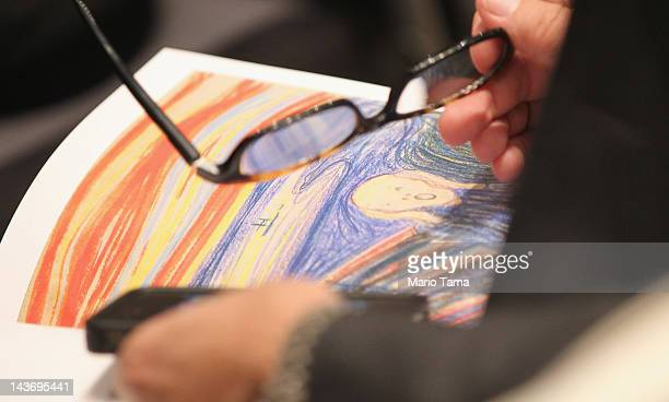 Person looks through a catalog as Edvard Munch's 'The Scream' is auctioned at Sotheby's May 2012 Sales of Impressionist, Modern and Contemporary Art...