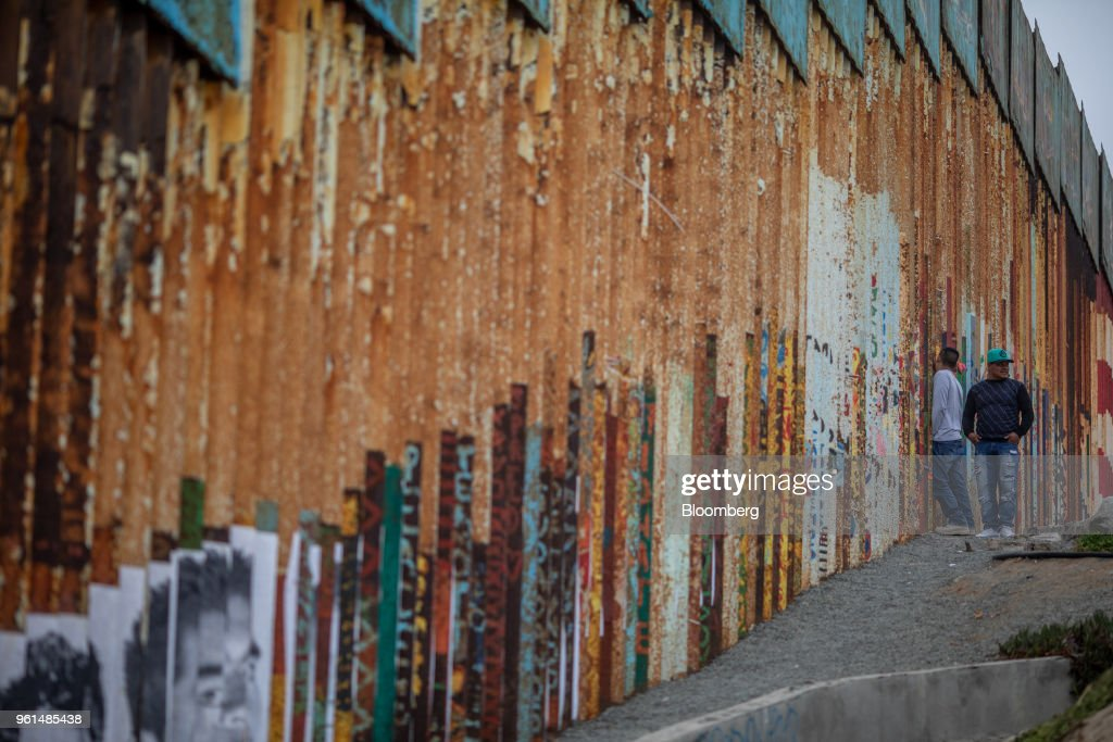 A person looks through a section of a U.S.-Mexico border wall in Tijuana, Mexico, on Monday, May 21, 2018. 'We won't care about threats of a wall,' National Regeneration Movement Presidential candidate Andres Manuel Lopez Obrador announced assuring another rally crowd in Zacatecas, one of the states that sends the most migrants to the U.S., that with him in power, they'll achieve equal footing with their neighbors to the north. Photographer: Alejandro Cegarra/Bloomberg via Getty Images