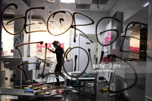 Person loots a T-Mobile store near the White House, as protests continue following the death of George Floyd, in Washington on Friday, May 29, 2020.