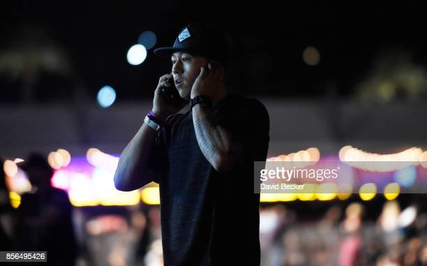 A person makes a call on his phone as people run from the Route 91 Harvest country music festival after apparent gun fire was heard on October 1 2017...