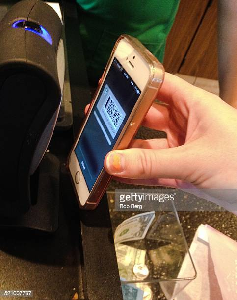 Santa Monica Ca October 19 2014 A person makes a contactless payment by positioning her iPhone 5 at a scanner in Starbucks
