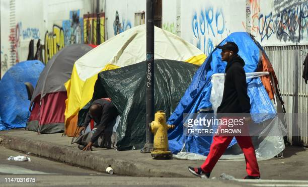 A person makes his way out of his tent among a row of tents along a sidewalk in downtown Los Angeles on May 30 2019 The city of Los Angeles on May 29...