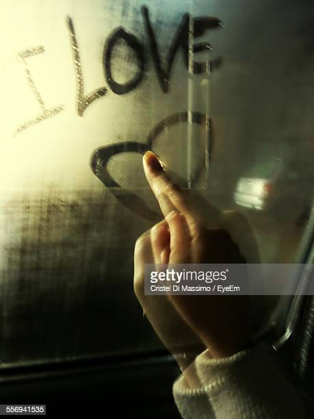 Person Making Heart Shape On Condensed Glass With Finger