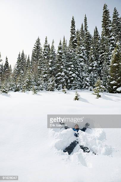 a person making snow angels - snow angel stock photos and pictures