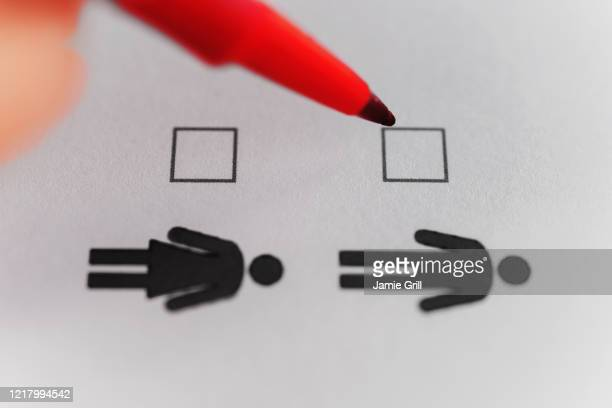 person marking with pen on male and female gender checklist - transgender stock pictures, royalty-free photos & images