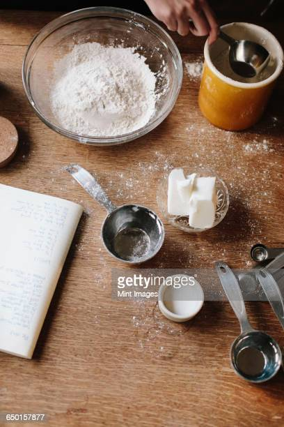 A person measuring ingredients, sugar, fat and flour on a table.