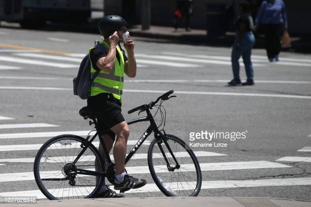 A person on a bicycle adjusts a face mask while waiting at a light on May 25 2020 in Westwood California Government guidelines encourage wearing a...