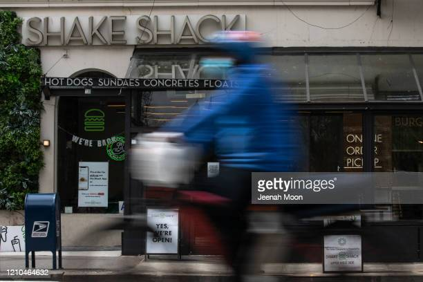 Person on a bicycle rides past a Shake Shack restaurant on April 20, 2020 in New York City. Shake Shack announce that they will return $10 million...