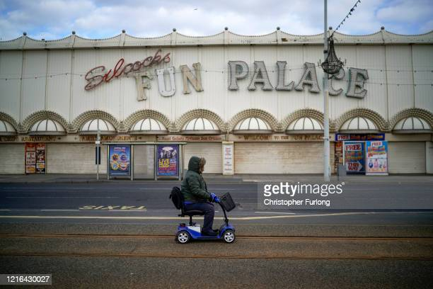 A person on a mobility scooter passes some attractions on Blackpool's Golden Mile which are closed as holiday makers locals and businesses observe...